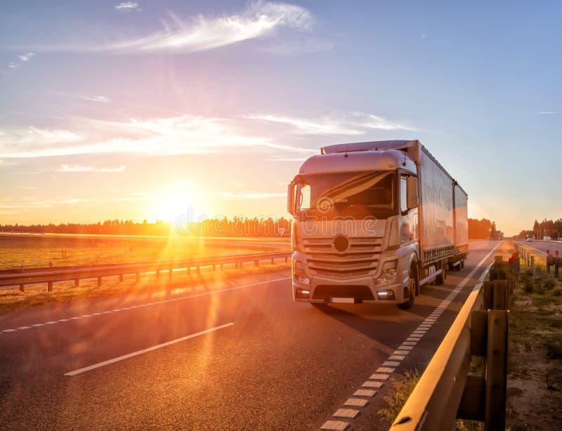 Den moderna vagnlastbilen transporterar last mot bakgrunden av en solnedgång Begreppet av lastbilsförare i fältet av frakter och arkivbilder