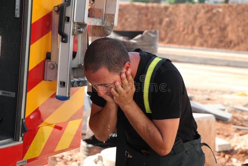 Den modiga brandmannen tvättar hans framsida royaltyfri fotografi