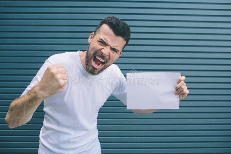 Den modiga mannen i den vita skjortan är stå och posera på kamera Han rymmer fingrar i grabb för näve rymmer också stycket av arkivbild