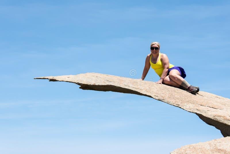 Den modiga unga fotvandraren för den vuxna kvinnan står överst av potatisen Chip Rock i San Diego California royaltyfri foto