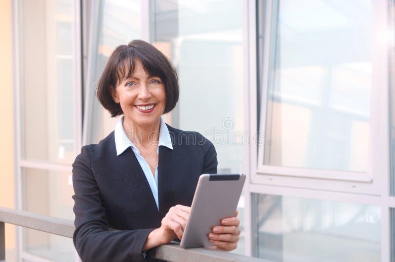 Den mogna affärskvinnan använder den trådlösa minnestavlan på den stads- gatan royaltyfria bilder