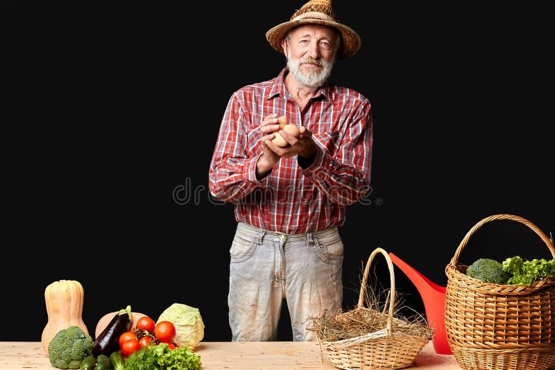 Den mogna bonden kom precis från hönacoopen som rymmer ny-lade ägg royaltyfri bild