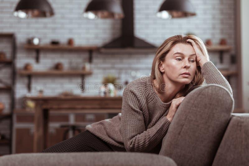 Den mogna familjkvinnan som sitter på soffakänslan, belastade royaltyfri foto