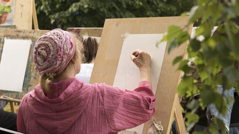 Den mogna kvinnan drar blom- skissar arkivfoto