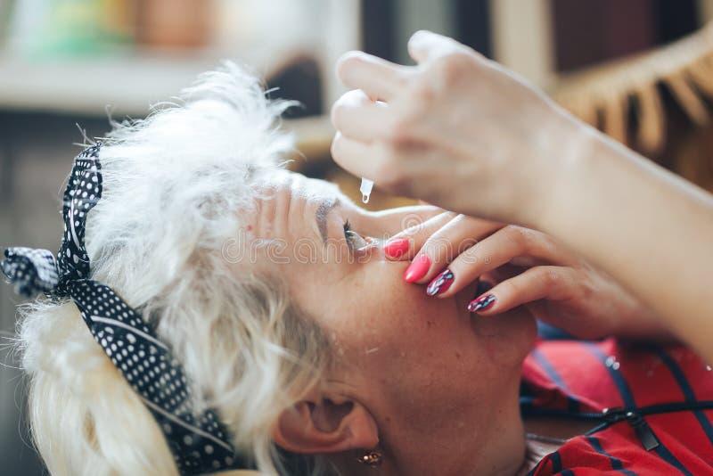 Den mogna kvinnan ger ögondropparna hemma royaltyfria foton