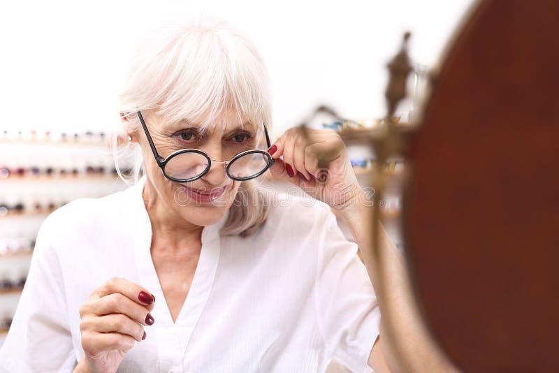 Den mogna kvinnan har en visiondefekt av åldringen fotografering för bildbyråer