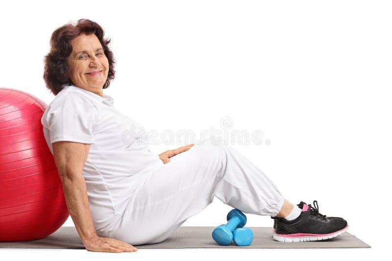 Den mogna kvinnan med pilates klumpa ihop sig och hantlar royaltyfria bilder