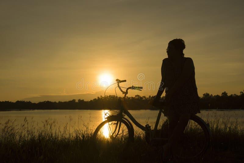 Den mogna kvinnan sitter på den retro tappningcykeln nära sjön på solnedgångögonblicket konturcykel på solnedgången med gräsfälte arkivfoton