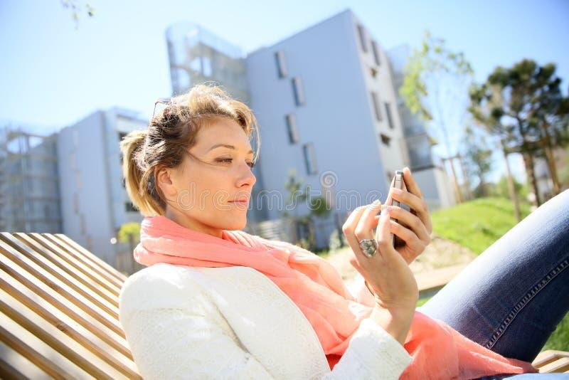 Den mogna kvinnan som in kopplar av, parkerar med smartphonen royaltyfria bilder
