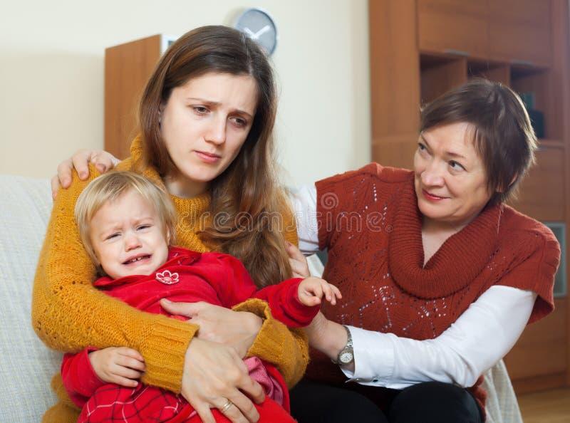 Den mogna kvinnan som tröstar den vuxna dottern med, behandla som ett barn arkivbilder