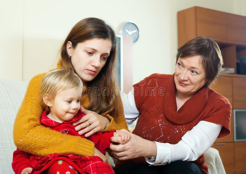 Den mogna kvinnan som tröstar den vuxna dottern med, behandla som ett barn royaltyfri bild