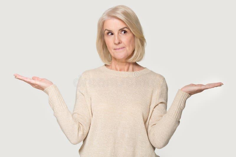 Den mogna kvinnan sträckte händer som att tänka gör val på vit bakgrund royaltyfri bild