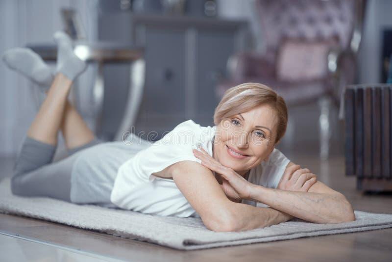 Den mogna kvinnan vilar, når han har öva yoga royaltyfri fotografi
