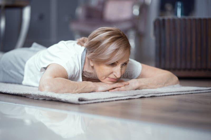 Den mogna kvinnan vilar, når han har öva yoga royaltyfri bild