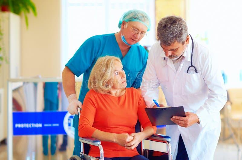 Den mogna kvinnliga patienten på rullstolen lyssnar till doktorsreceptläkarbehandlingen royaltyfria foton