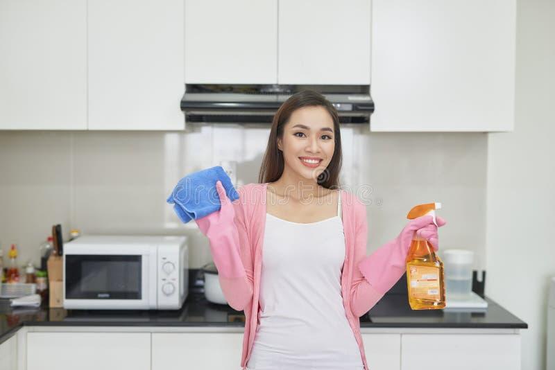 Den mogna kvinnlign att bry sig omkring rent av kök på hennes hus royaltyfri fotografi