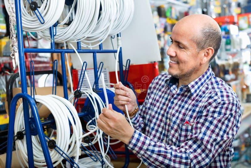 Den mogna manliga realiteten tillfredsställde kabel för kundköpandeutsida arkivbild