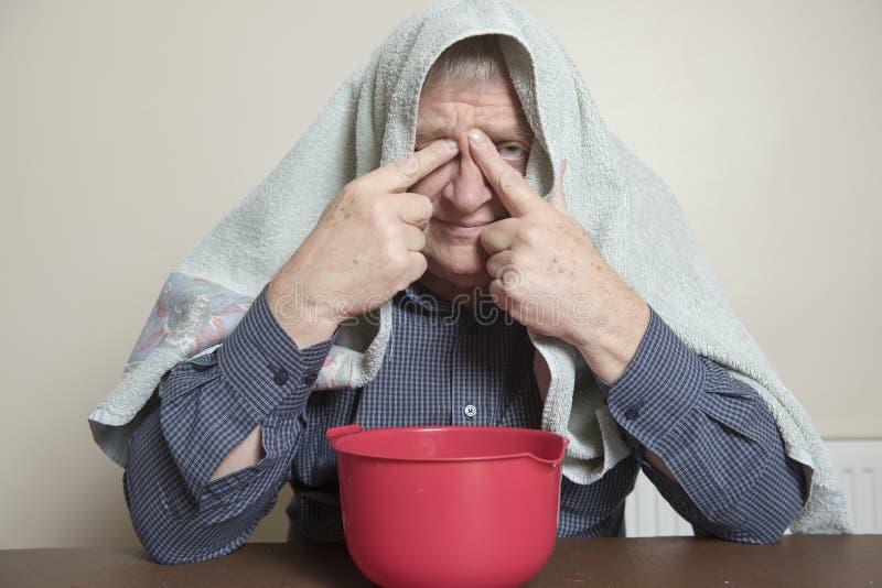 Den mogna mannen med en förkylning och en bihåla utfärdar inhalation av ånga royaltyfri fotografi