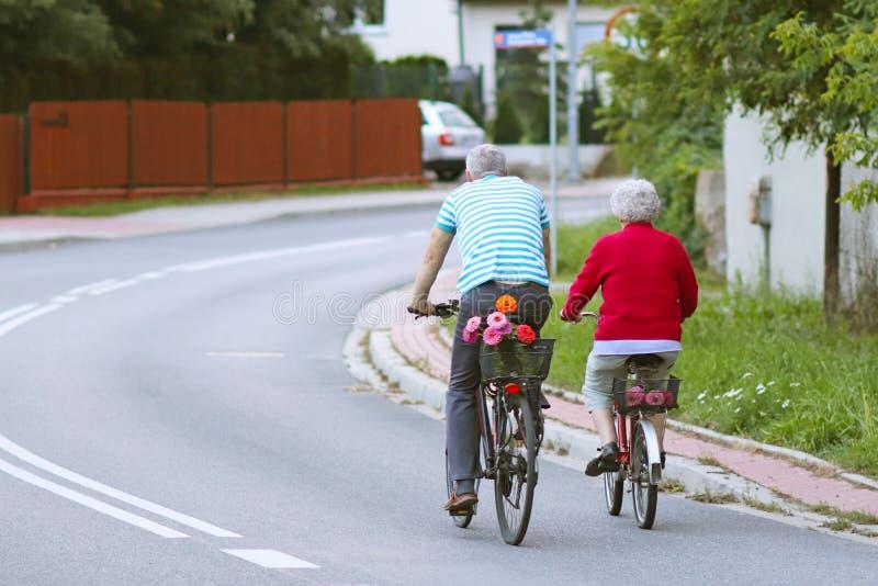 Den mogna mannen och kvinnan rider en cykel bland gräsplanerna En sund och aktiv del av liv Ekologisk transport för befolkningen royaltyfria foton