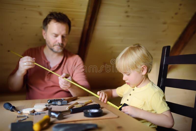 Den mogna mannen och pysen gör en träleksak tillsammans Fadern lär hans sonarbete med hjälpmedel Traditionell utbildning av pojke royaltyfria bilder