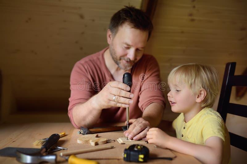 Den mogna mannen och pysen gör en träleksak tillsammans Fadern lär hans sonarbete med hjälpmedel Traditionell utbildning av pojke royaltyfri fotografi