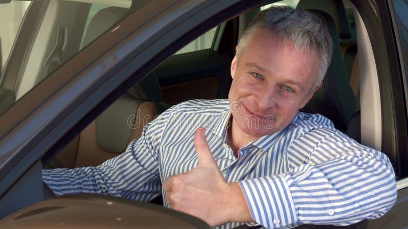 Den mogna mannen sitter in i bilen på återförsäljaren arkivfoto