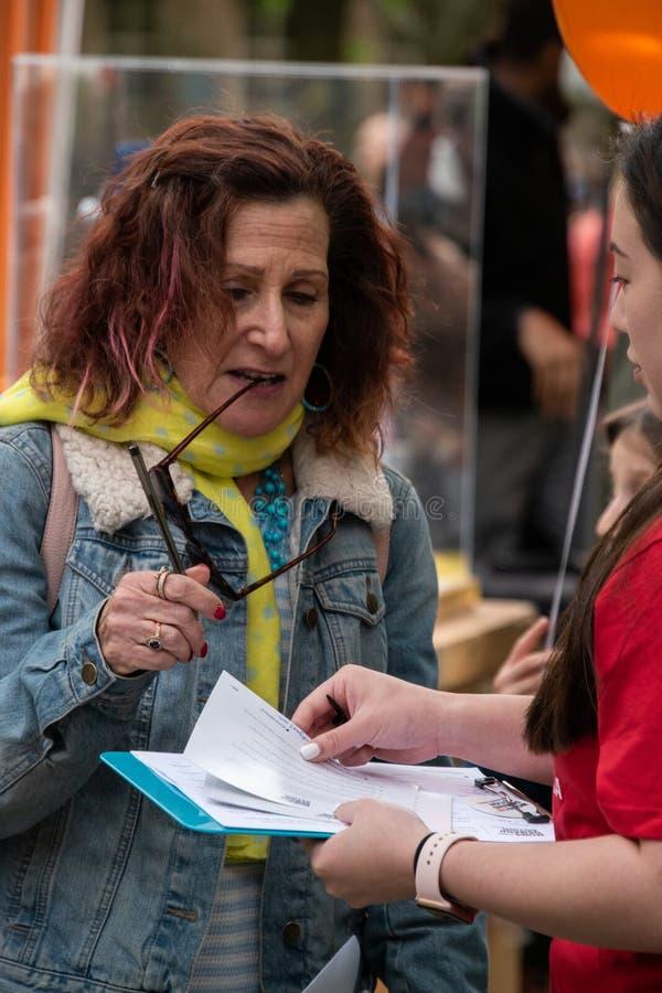 Den mogna person född under en baby boomkvinnan som undertecknar en begäran för mammor, begär handling på vapenkontroll på en gat arkivfoton