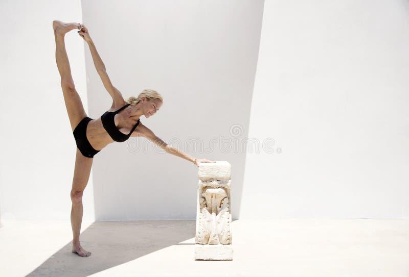 Den mogna yogakvinnan i jonisk kolonnstötta stöttade Asana royaltyfria bilder