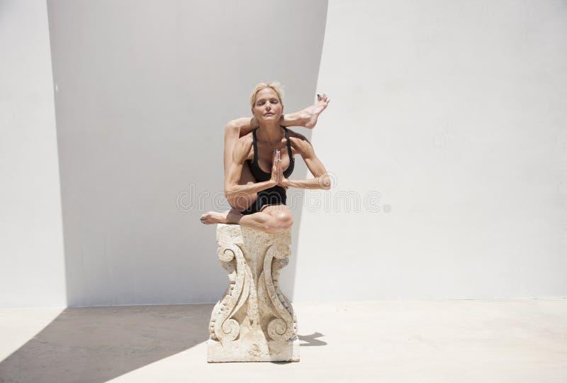 Den mogna yogakvinnan i jonisk kolonnstötta stöttade Asana royaltyfri fotografi