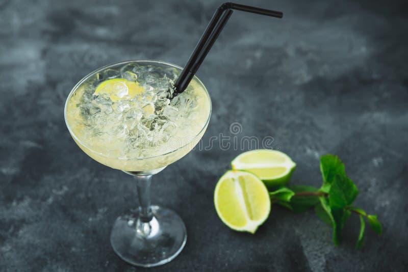 Den Mojito coctailen i exponeringsglas och limefrukt bär frukt på en tabell Sommar arkivfoton