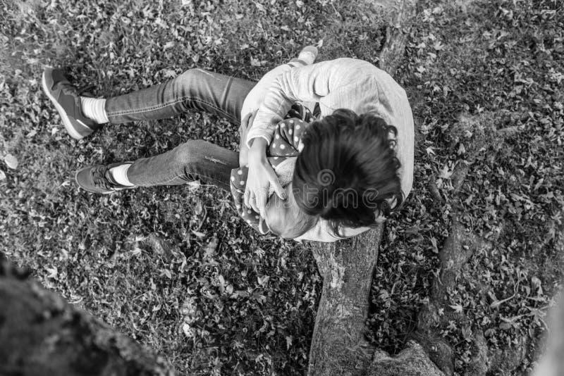 Den monokromma bilden av modern som ammar som är hennes, behandla som ett barn flickan arkivbilder