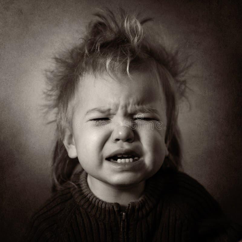 Den monokromma ståenden av en gråt behandla som ett barn arkivfoto
