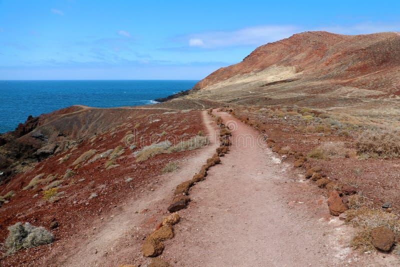 Den Montana Roja Red bergbanan i vulkaniskt område med rött vaggar och jord, jordlavafältet, El Medano, Tenerife arkivbilder