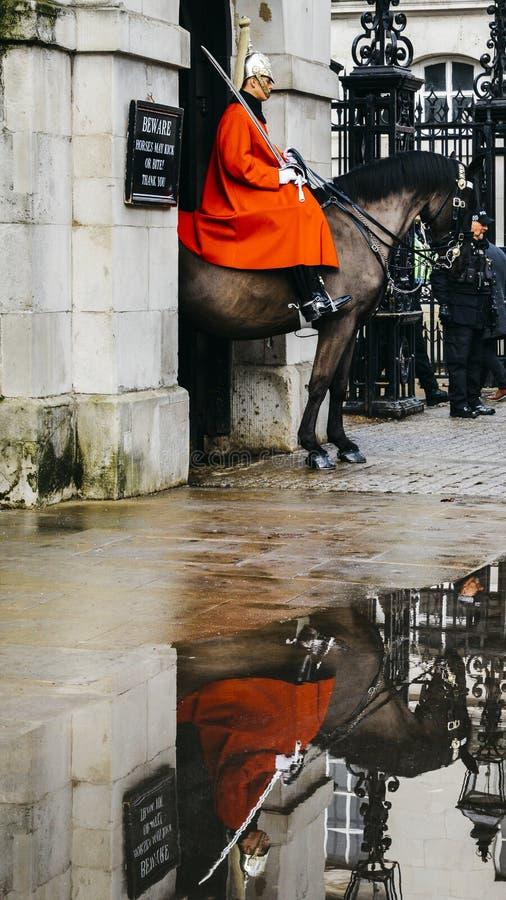 Den monterade brittiska vakten på häst på hästvakter ståtar jordning på Whitehall, reflexion på pöl - den London turisten royaltyfri fotografi