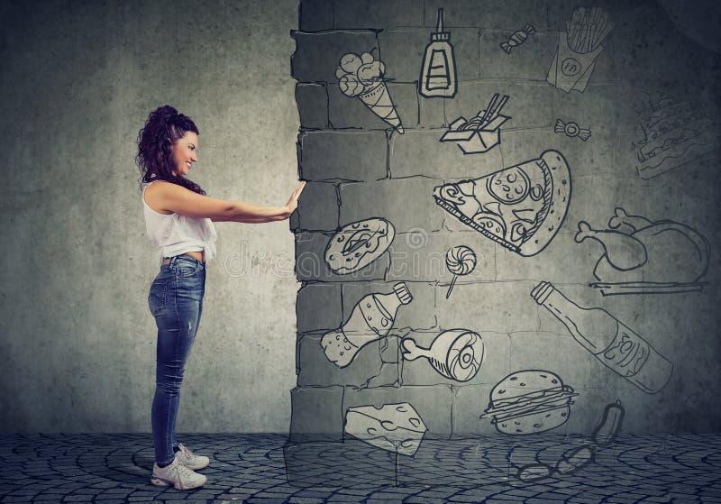 Den motiverade unga kvinnan som motstår frestelse av att äta den snabba foten och att välja som är bättre, bantar arkivbilder