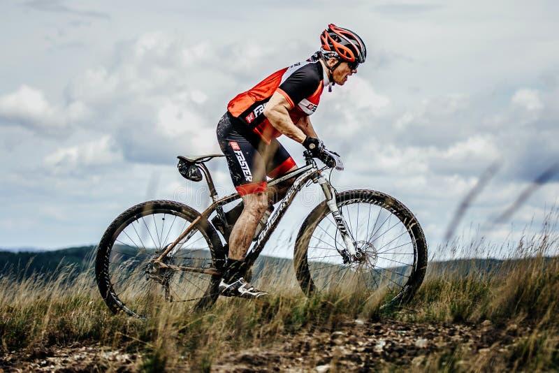 Den Mountainbiker cyklisten rider på slingaöverkant av berget royaltyfri fotografi
