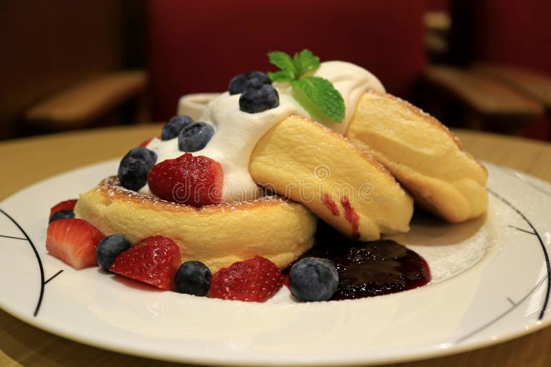Den Mouthwatering fluffiga Soufflepannkakan med nya piskade kräm- och blandningbär tjänade som på den vita plattan royaltyfria foton