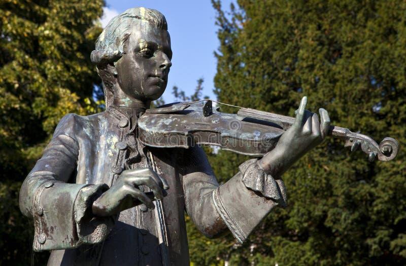 Den Mozart statyn ståtar in trädgårdar, bad royaltyfri bild