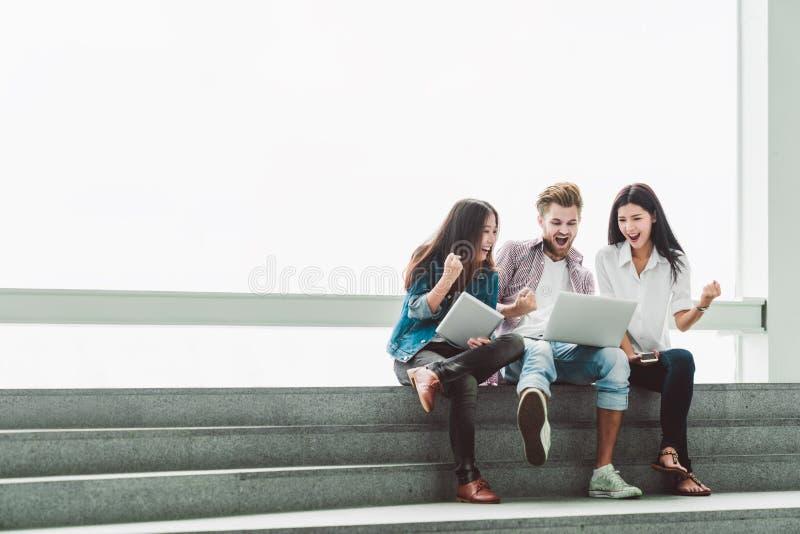 Den multietniska gruppen av högskolestudenter eller frilanscoworkers firar samman med bärbara datorn och minnestavlan Idérik elle royaltyfri fotografi