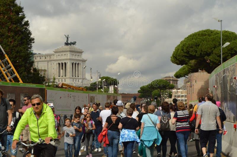 Den multinationella folkmassan av turister på en fot- gata i mitten av Rome går till altaret av fäderneslandet eller Vittorianoen arkivfoton