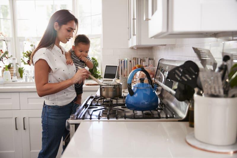 Den Multitasking mumen som rymmer hennes ungt, behandla som ett barn, medan hon gör mat på hoben i hennes kök, sidosikten royaltyfri foto