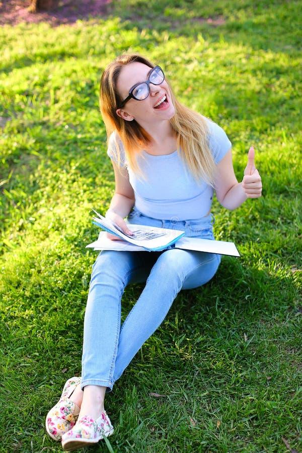 Den muntra visningen för kvinnlig student tummar upp att studera in parkerar och att sitta på grönt gräs arkivbild