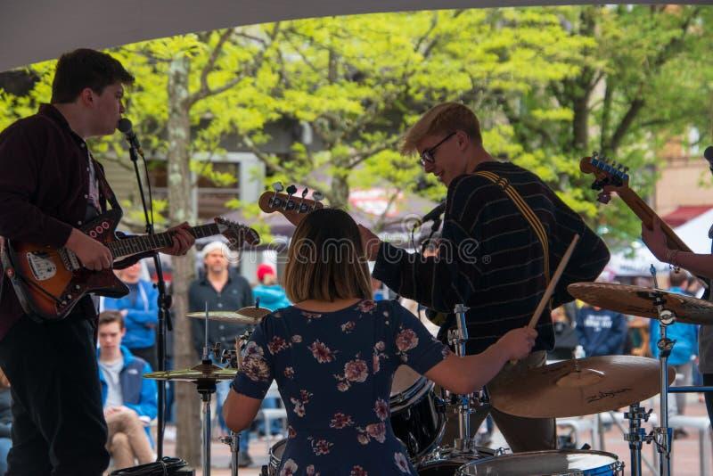 Den musikaliska gruppen ses från baksidan, som de spelar deras instrument framme av en folkmassa på en utomhus- mässa Det finns e fotografering för bildbyråer