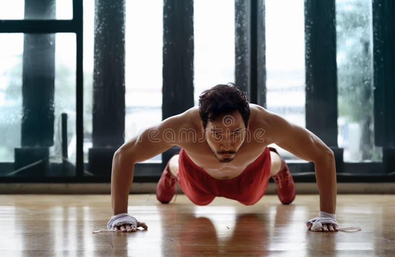 Den muskulösa asiatiska mannen som att göra skjuter, ups arkivfoton