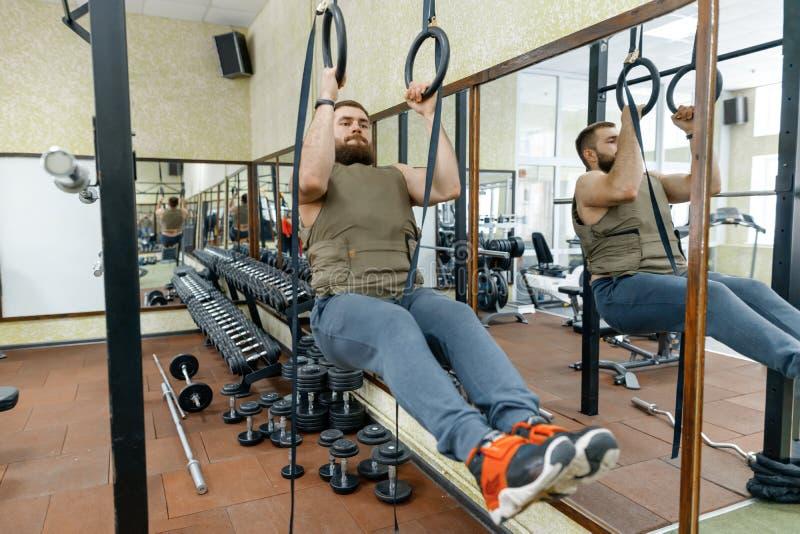 Den muskulösa caucasian skäggiga mannen som gör vägt iklätt för övningar, tilldelar idrottshallen, militär stil arkivfoton