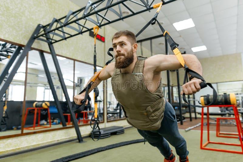 Den muskulösa caucasian skäggiga mannen som gör vägt iklätt för övningar, tilldelar idrottshallen, militär stil arkivbilder