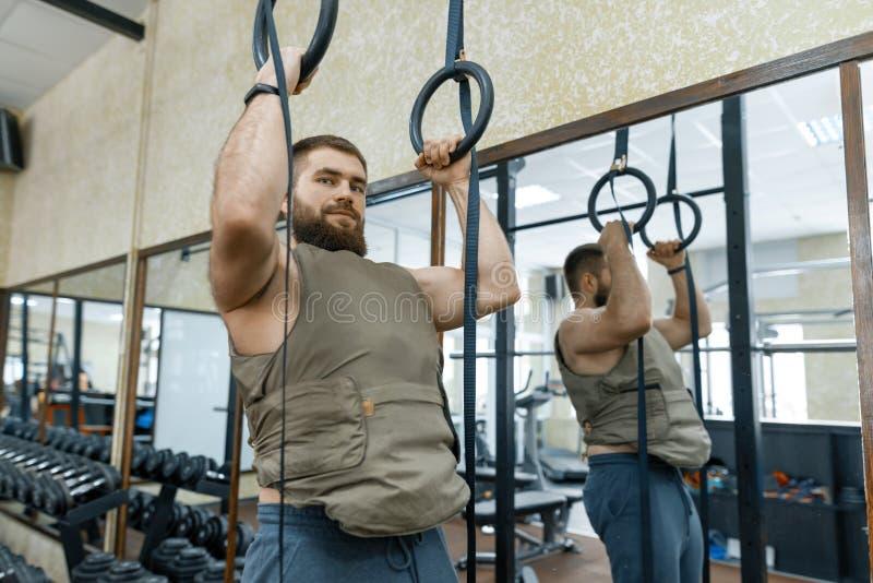 Den muskulösa caucasian skäggiga mannen som gör vägt iklätt för övningar, tilldelar idrottshallen, militär stil royaltyfri foto