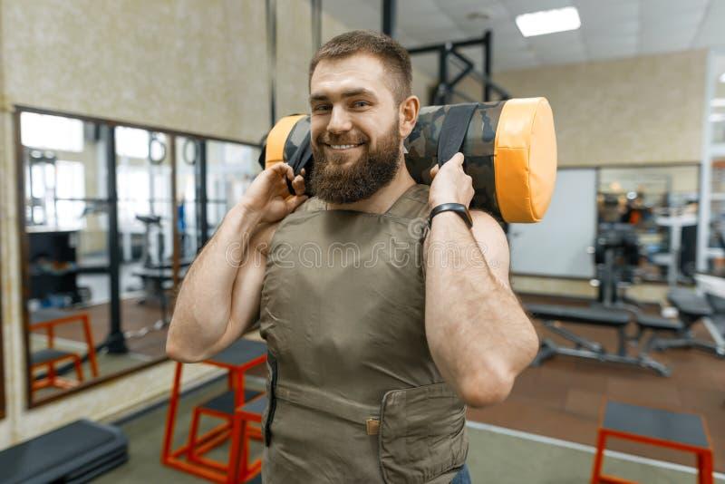 Den muskulösa caucasian skäggiga mannen som gör vägt iklätt för övningar, tilldelar idrottshallen, militär stil royaltyfri fotografi