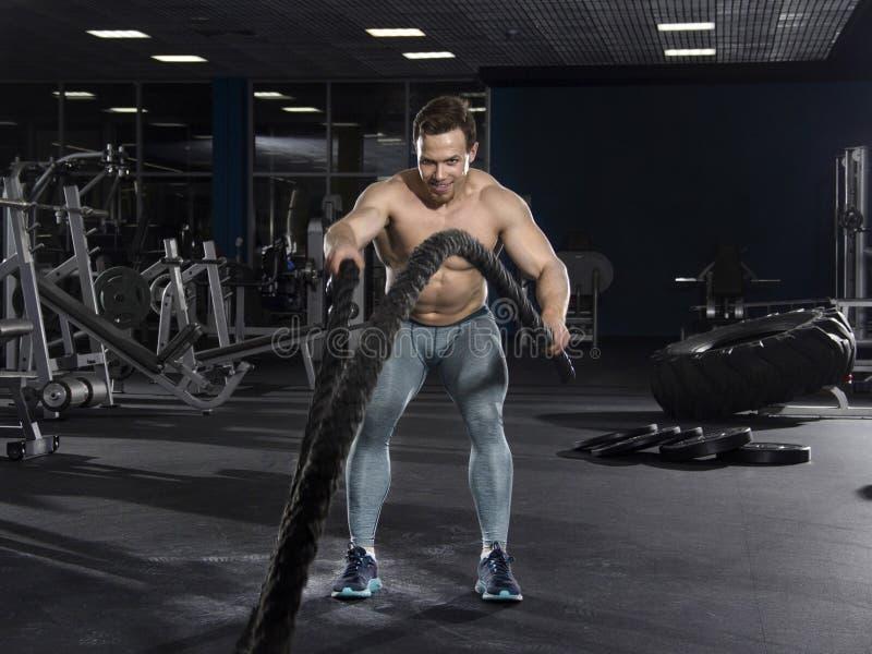 Den muskulösa idrottsman nen med stridrep övar i modern konditionce arkivbild