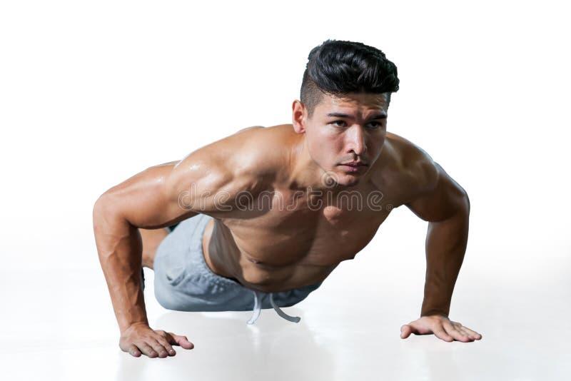 Den muskulösa kroppsbyggaremannen som att göra skjuter, ups övningen som isoleras på vit bakgrund med urklippbanan Ung sport för  royaltyfri fotografi